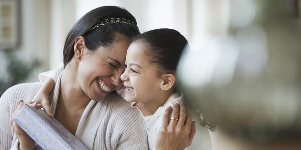 Mãe sorridente acaricia com o próprio rosto, o rosto da filha que acaba de lhe entregar um presente no Dia das Mães