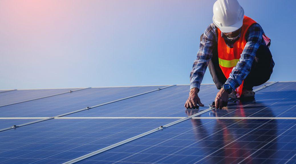 Em cima de telhado com placas fotovoltaicas, integrador solar faz trabalho de instalação