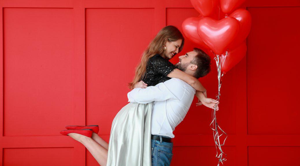 Para falar de vendas no Dia dos Namorados, homem abraça e ergue uma mulher, que segura balões de coração vermelho
